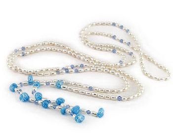 Pärlhalsband i vita odlade sötvattenpärlor och blåa kristaller. Pärlhalsbandet är gjort i risformade 4x5mm sötvattenpärlor.