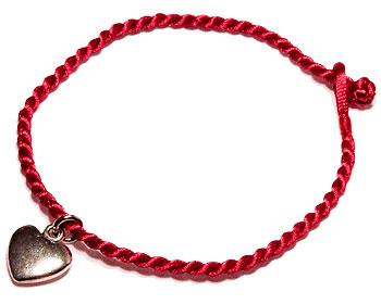 Smyckeshjärta på rött armband. Längd cirka 16-17 cm.