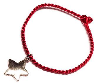 Stjärnarmband på röd tråd. Längd cirka 16-17 cm.