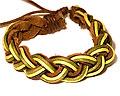 Armband i läder och gråna trådar.