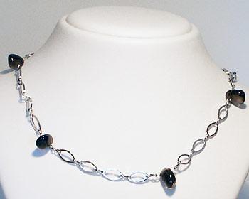 Halsband med mörka halvädelstenar.