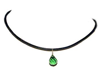 Halsband med en svart läderrem och med en grön halvädelsten som hänge.