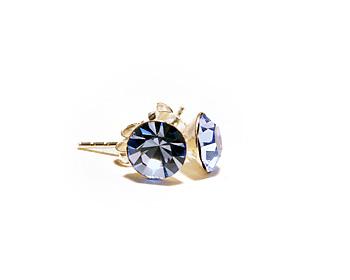 Örhängen med 6mm kristaller som motsvarar december månad (blue zircon). Silverstift.