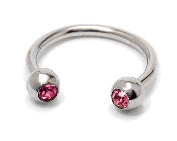 Billig piercing i kirurgiskt stål. Tjocklek cirka 1,2 mm, diameter cirka 10 mm.