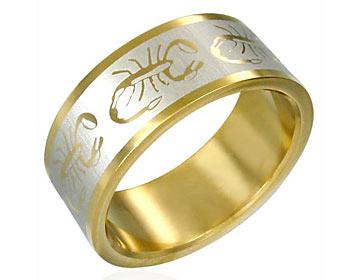 Guldplätterad ring gjord i kirurgiskt stål med skorpioner. Bredd cirka 8 mm.